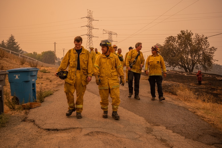Firefighters walking on a road.