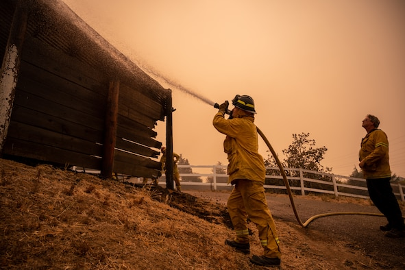A firefighter puts out a fire with a hose.
