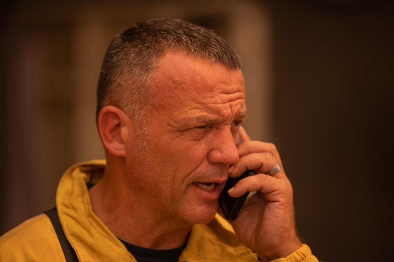 A fire chief talks on the phone about information regarding the fire.