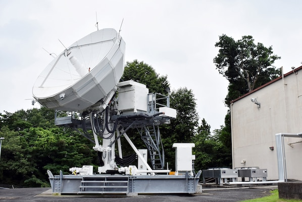 A satellite terminal stands outside a building.