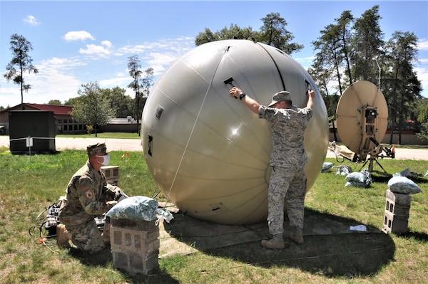 Airmen adjust a communications satellite system.