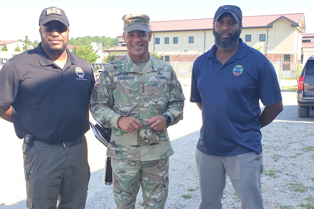 Two civilian men in blue polos stand next to a military man for a photo op