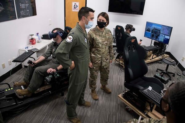 Chief Master Sgt. of the Air Force JoAnne S. Bass speaks with Capt. Orion Kellogg, 559th Flying Training Squadron instructor pilot, about the use of the virtual reality flight simulators for flying training during a tour of Undergraduate Pilot Training 2.5 Aug. 20, 2020, at Joint Base San Antonio-Randolph, Texas. Bass, along with Secretary of the Air Force Barbara Barrett and Chief of Staff of the Air Force Gen. Charles Q. Brown Jr., visited  Air Education and Training Command's accelerated pilot training program that combines student-centered learning with integrated immersive technology, seamless access to content and quality instruction.