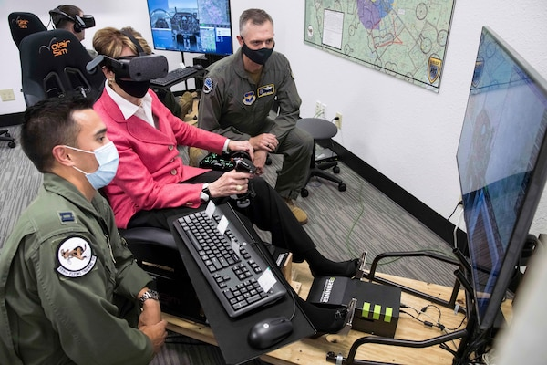 Secretary of the Air Force Barbara Barrett uses a virtual reality flight simulator as U.S. Air Force Capt. Orion Kellogg (left) and Maj. Gen. Craig Wills, 19th Air Force commander (right), look on  during her visit to Undergraduate Pilot Training 2.5 Aug. 20, 2020, at Joint Base San Antonio-Randolph, Texas. Barrett, along with Chief of Staff of the Air Force Charles Q. Brown Jr., and Chief Master Sgt. of the Air Force JoAnne Bass toured Air Education and Training Commands UPT 2.5  program, which scales lessons learned from Pilot Training Next as part of their first joint visit.