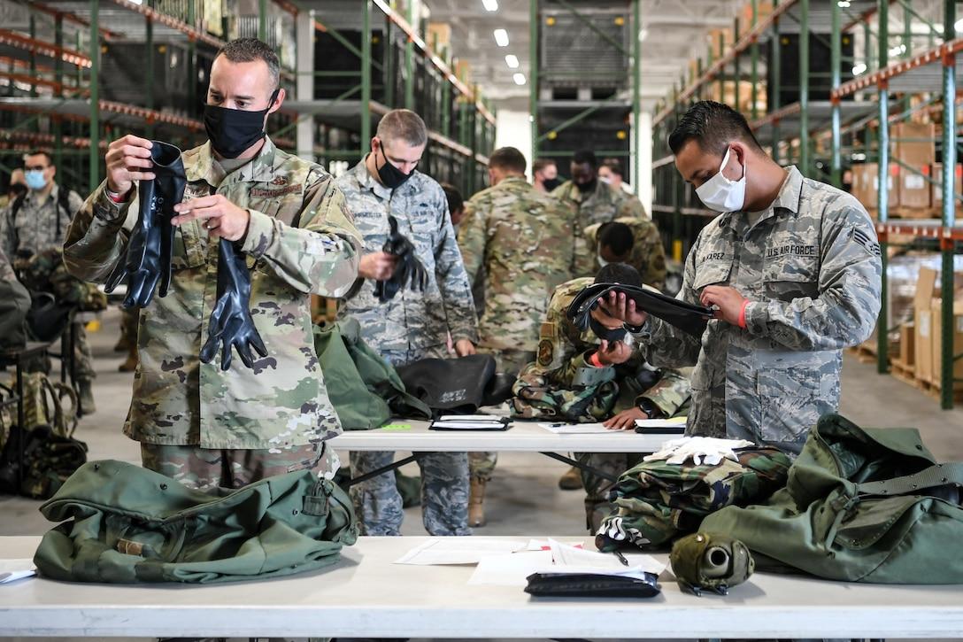 Dozens of Airmen check their deployment gear on tables.
