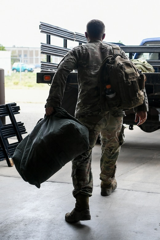 An Airman throws his deployment bag into the back of a flatbed truck.