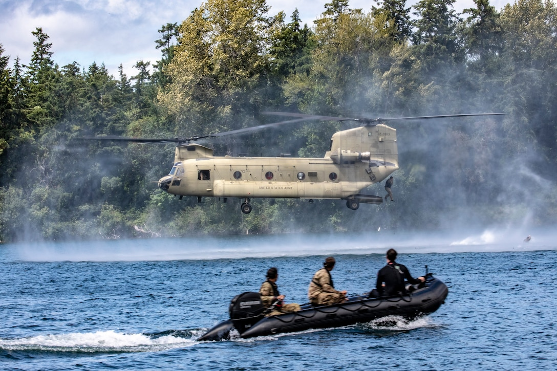 A soldier jumps into a lake from a helicopter while other troops in a rubber boat move through the water.