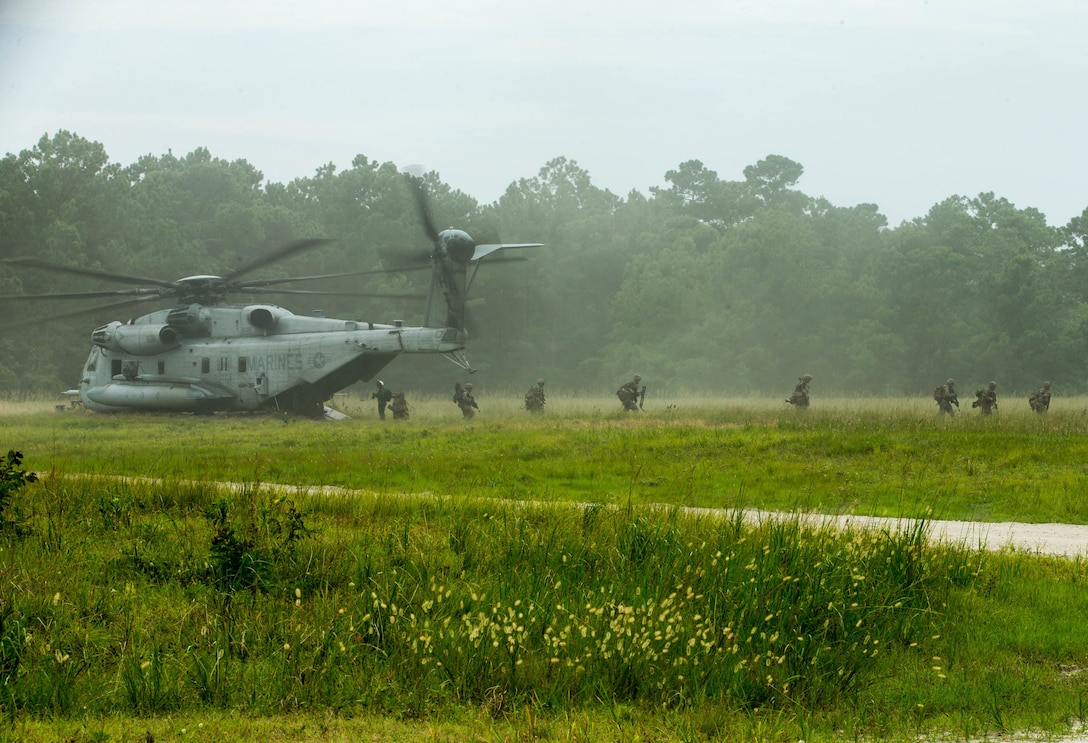 Marines exit a helicopter in a lush green field.