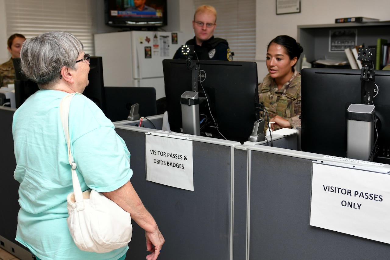 A woman poses for an ID card photo.