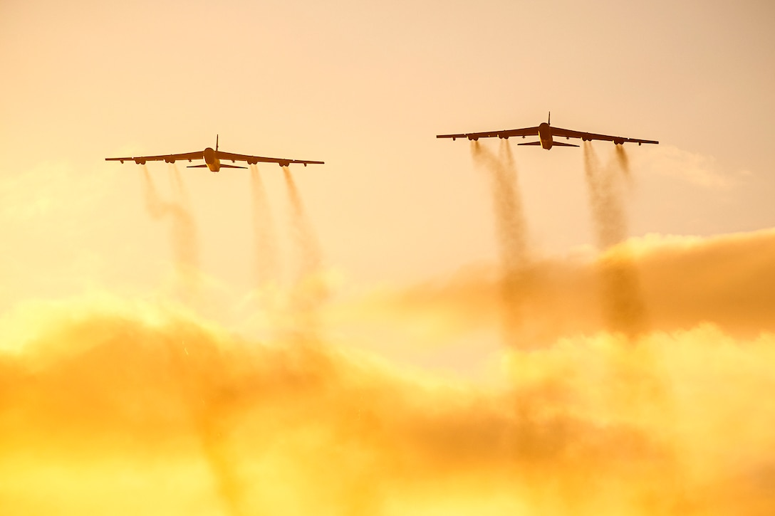 Two Air Force Stratofortress aircraft fly in an orangish-pink sky, leaving contrails.