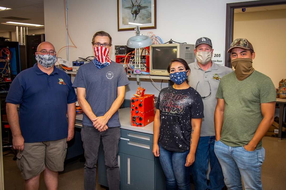 The 411th Flight Test Squadron instrumentation team: Brian Bock, Jackson Greaves, Valerie Galvan, Mike Burgess and James Lee (left to right) pose for a photo with a Common Range Integrated Instrumentation System module at Edwards Air Force Base, Aug. 19. The CRIIS was successfully integrated into a 411th FLTS F-22 Raptor, Aug. 5. (Photo courtesy of Kyle Larson, Lockheed Martin)