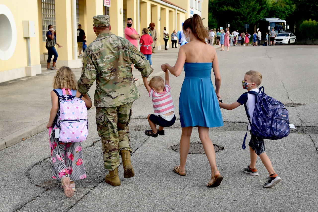 Three children and their parents hold hands as they walk together.