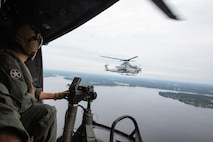 Cpl. Bryce Hawkins, an aerial observer with Marine Light Attack Helicopter Squadron 269, flies in a UH-1Y Huey next to an AH-1Z Viper during Exercise Deep Water 2020 over Marine Corps Air Station New River, North Carolina, July 29, 2020. The purpose of the exercise is to increase 2nd Marine Aircraft Wing's interoperability and readiness on a scale that simulates peer-level threats. (U.S Marine Corps Photo by Cpl. Juan C. Dominguez)