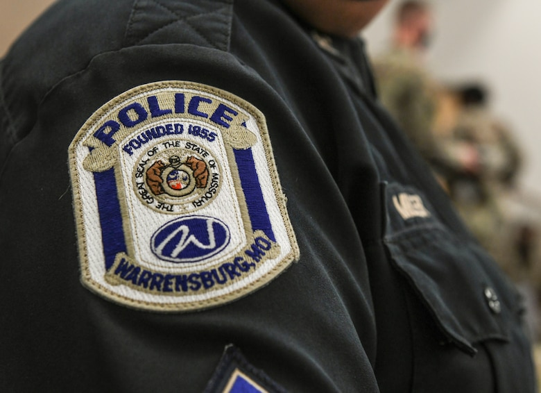 A Warrensburg Police Department law enforcement member displays a WPD uniform patch during an Airman Leadership School graduation, Aug. 14, 2020, at Whiteman Air Force Base, Missouri. For the first time, Whiteman AFB's ALS class included two local law enforcement personnel who attended the leadership course and earned certificates of completion. Airman Leadership School is the first level of the Enlisted Professional Military Education continuum and prepares Senior Airmen to be professional, war-fighting Airmen and Space professionals who can supervise and lead work teams. (U.S. Air Force photo by Staff Sgt. Sadie Colbert)