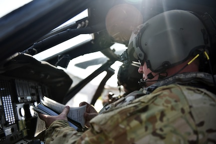 U.S. Army Chief Warrant Officer 2 Kristopher Pinson, a pilot assigned to the 1st Battalion 228th Aviation Regiment Air Ambulance Detachment at Joint Task Force-Bravo, checks his pre-flight technical orders at Soto Cano Air Base, Honduras July 31, 2020. The Charlie Company of the 1-228th have been vital in providing emergency medical transportation throughout Honduras. Pinson served as a co-pilot in the second aeromedical evacuation mission.