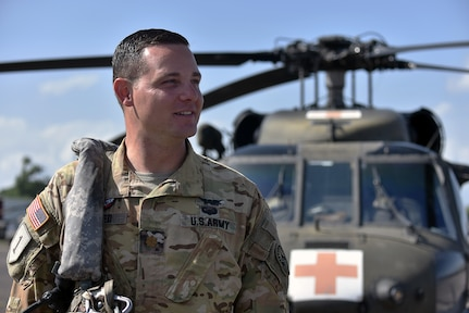 U.S. Army Maj. Cody Sneed, the 1st Battalion 228th Aviation Regiment Joint Task Force-Bravo Charlie Company commander, stands in front of a UH-60 Blackhawk at Soto Cano Air Base, Honduras July 31, 2020. The Charlie Company of the 1-228th have been vital in providing emergency medical transportation throughout Honduras.