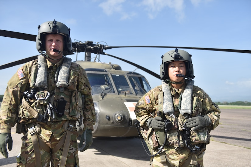 U.S. Army Capt. Richard Jackson (left), a flight doctor assigned to the 1st Battalion 228th Aviation Regiment Air Ambulance Detachment at Joint Task Force-Bravo, and U.S. Army Staff Sgt. Steven Thai (right), a flight medic assigned to the 1st Battalion 228th Aviation Regiment Air Ambulance Detachment at Joint Task Force-Bravo, poses in front of a UH-60 Blackhawk  at Soto Cano Air Base, Honduras July 31, 2020. Jackson and Thai are two members of the crew who provided lifesaving medical care during a Jul.14 mission. The 1-228 Charlie Company is comprised of just 20 members and is the only aeromedical evacuation in the U.S. Southern Command area of responsibility.