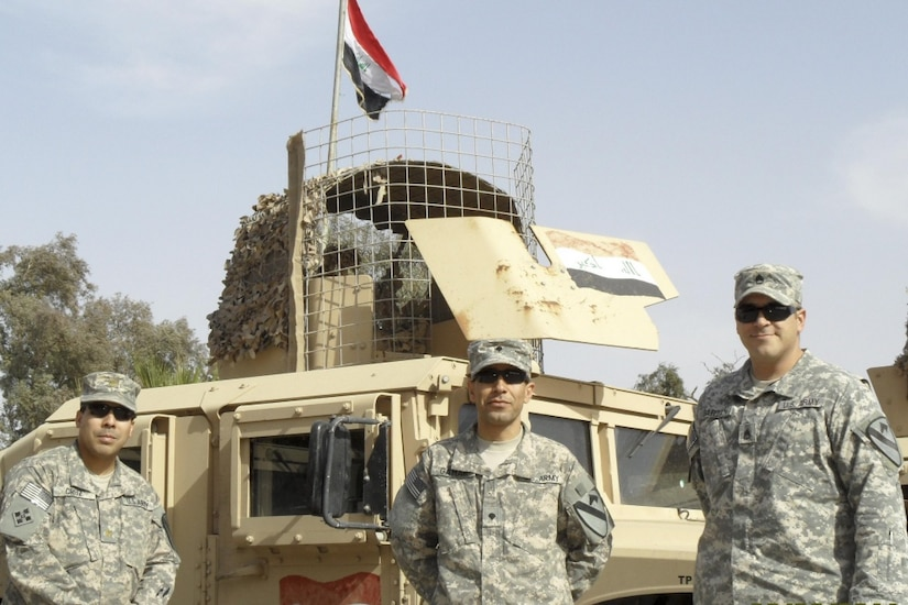 Three soldiers stand in front of a military vehicle.