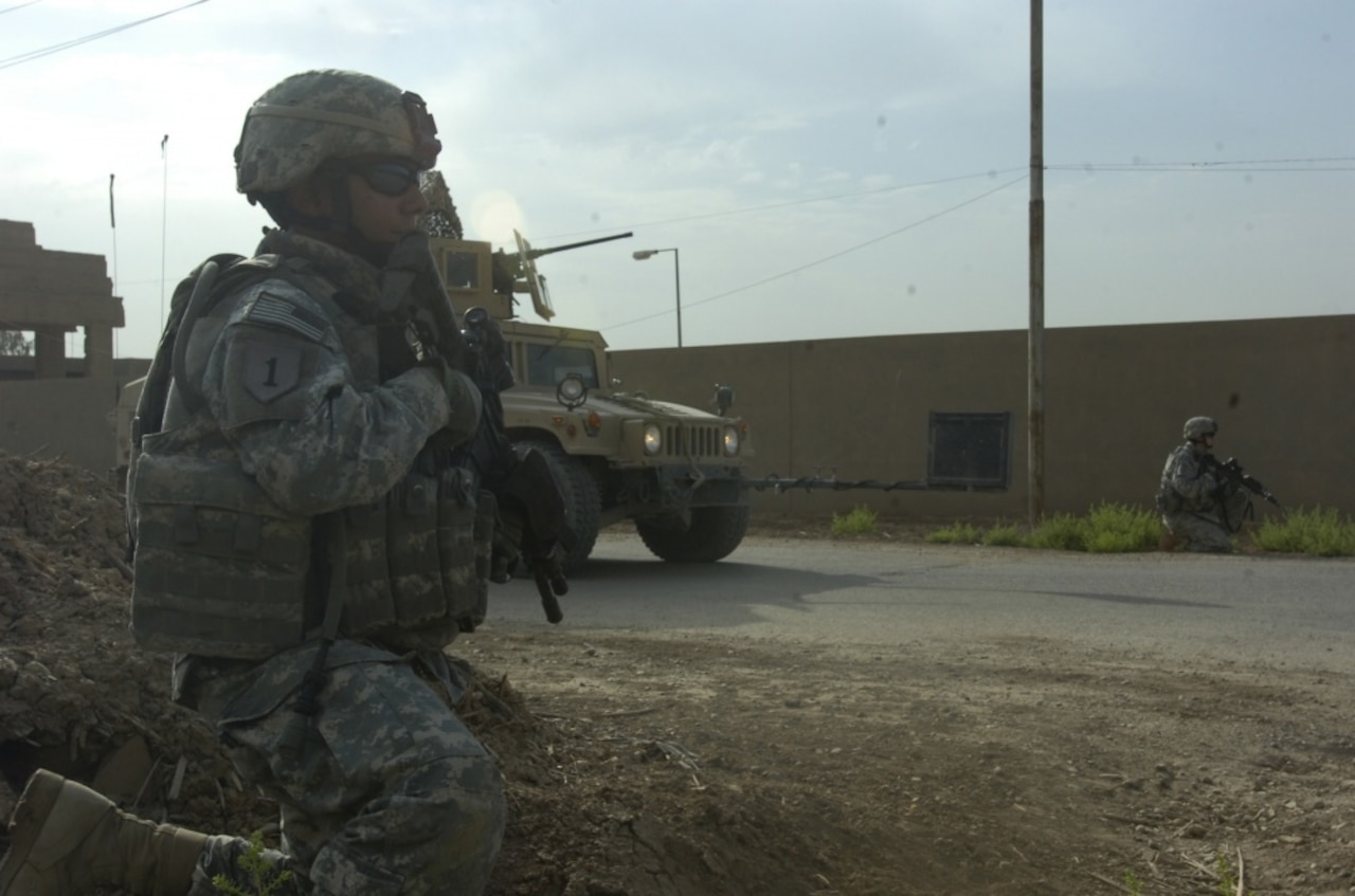 A soldier kneels while on patrol.