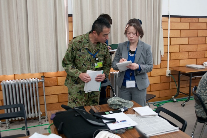 An interpreter goes over notes with a man in a military uniform.