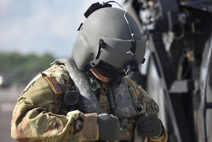 U.S. Army 1st Lt. Ian Gidcomb, a pilot assigned to the 1st Battalion 228th Aviation Regiment Air Ambulance Detachment at Joint Task Force-Bravo, secures his flight vest at Soto Cano Air Base, Honduras July 31, 2020. Gidcomb served as a co-pilot in the third aeromedical evacuation mission.