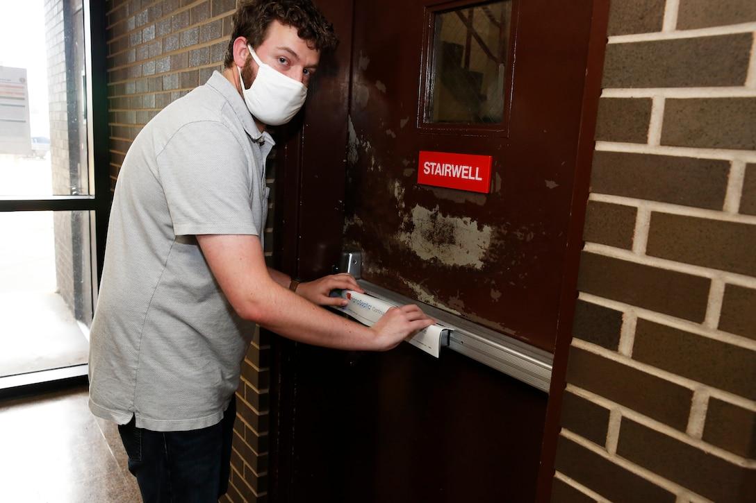 An engineer applies a NanoSeptic protective sheet to a door.