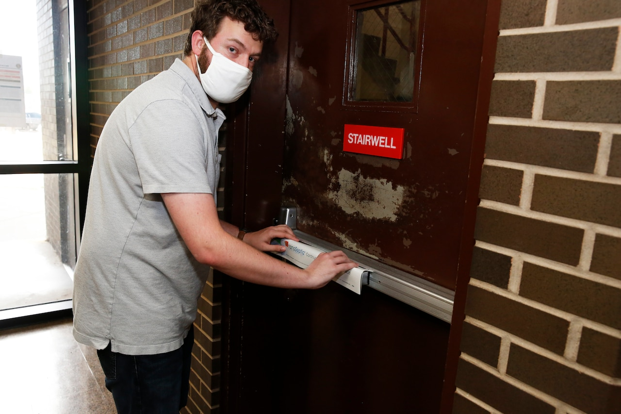 An engineer applies a NanoSeptic protective sheet to a door.