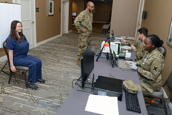 Spc. Shunterika Fields and Army Pvt. Stephen Hines create ID cards to track non-patient personnel's temperatures at the temporary medical facility in New Orleans, April 4.