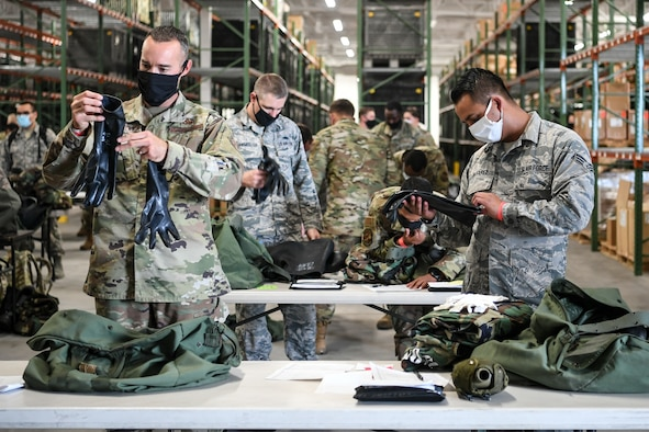 Dozens of Airmen check their deployment gear on tables.
