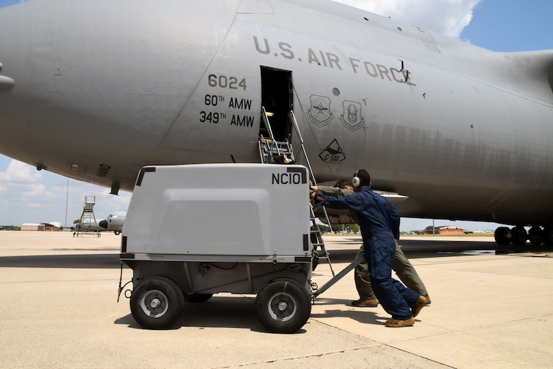 Staff Sgt. Michael Hailemaskel and Senior Airman Glenn C. Bovino II, both with the 60th Aircraft Maintenance Squadron at Travis Air Force Base, California, move an aircraft ground support cart so the C-5M Super Galaxy can depart the airfield Aug. 24, 2020 at Joint Base San Antonio-Lackland, Texas.