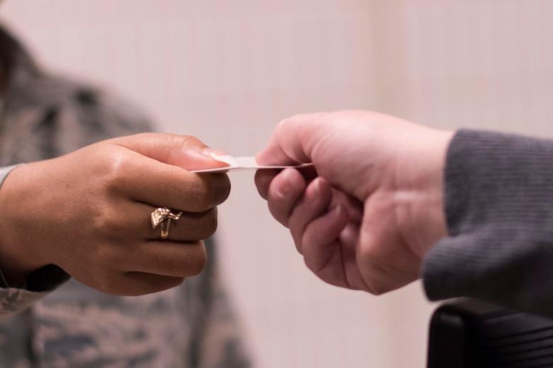 An airman hands an ID card to a family member.