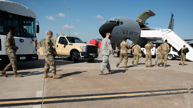 Several Airmen walk off of a bus and walk towards a KC-135 Stratotanker parked on the Incirlik Air Base flight line, August 17, 2020.