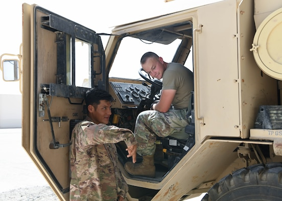Army Specialist Jose Arellano (left), instructor for the 133rd Battalion, gives instructions to lift the pallet of the M1075 Palletized Load System, as Air Force Senior Airman Aiden Penrod, 380th Expeditionary Logistics Readiness Squadron ground transportation apprentice, looks on, July 22, 2020, at Al Dhafra Air Base, United Arab Emirates.