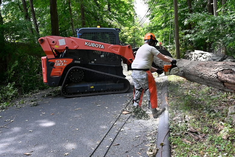 Air Force Master Sgt. Jon Delaney, member of the 103rd Civil Engineer Squadron, uses a chainsaw to cut a tree that fell into a roadway during Hurricane Isaias, August 7, 2020, Fairfield, Connecticut. Delaney and other members of the 103rd CES removed fallen trees and other debris  from roadways as part of Connecticut's emergency response to Isaias. (U.S. Air National Guard photo by Tech. Sgt. Tamara R. Dabney)