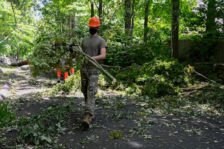 A member of the 103rd Civil Engineer Squadron removes branches from a tree that fell into a roadway during Hurricane Isaias, August 7, 2020, Fairfield, Connecticut. The 103rd CES was one of multiple Connecticut Guard units to provide disaster relief in response to Isaias. (U.S. Air National Guard photo by Tech. Sgt. Tamara Dabney)