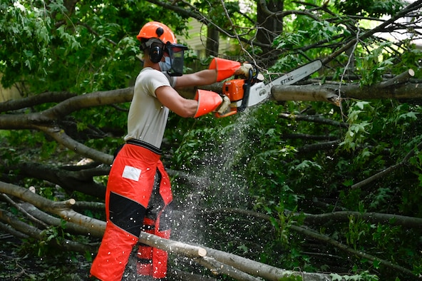 Senior Airman John Donnelly, III, member of the 103rd Civil Engineer Squadron, uses a chainsaw to cut a tree that had fallen into a roadway during Hurricane Isaias, August 8, 2020, Fairfield, Connecticut. The 103rd CES was one of multiple Connecticut Guard units to provide disaster relief in response to Isaias. (U.S. Air National Guard photo by Tech. Sgt. Tamara Dabney)