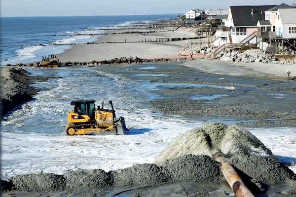 Bulldozer pushes sand from the ocean to the shore.