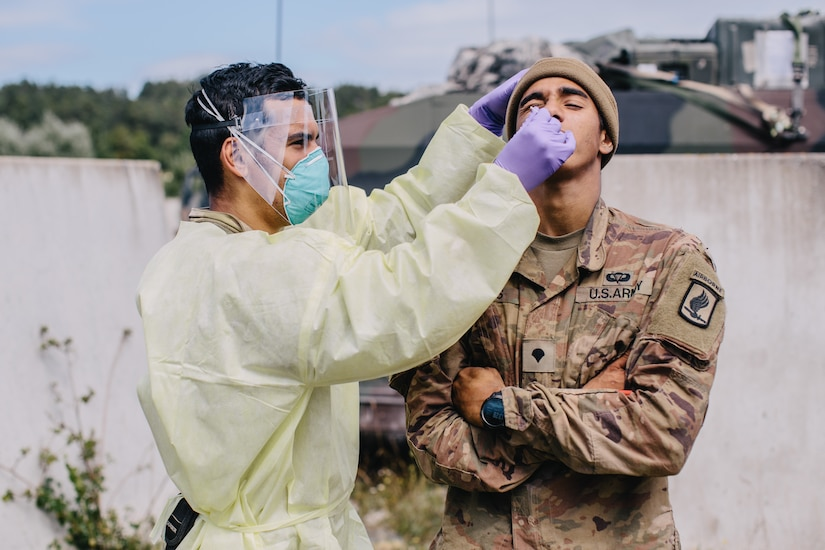 An army medic in full protective gear tests a soldiers for COVID-19.