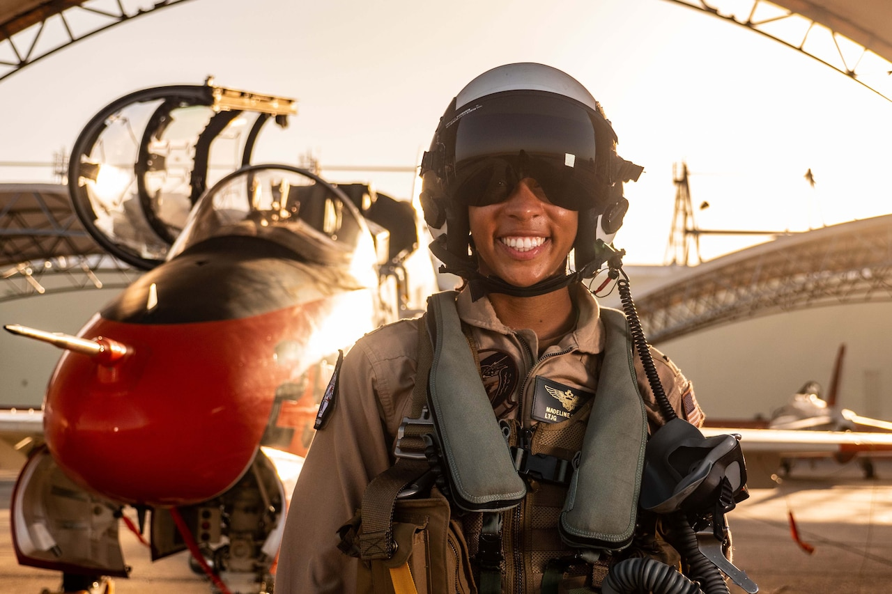 A pilot with a helmet on stands in front of a jet near a hangar.