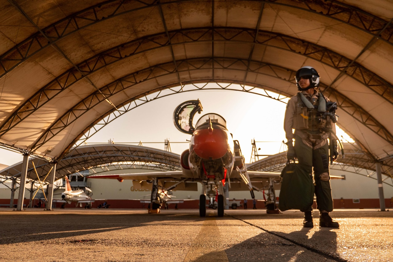 A pilot in combat gear stands beside a jet in a hangar.