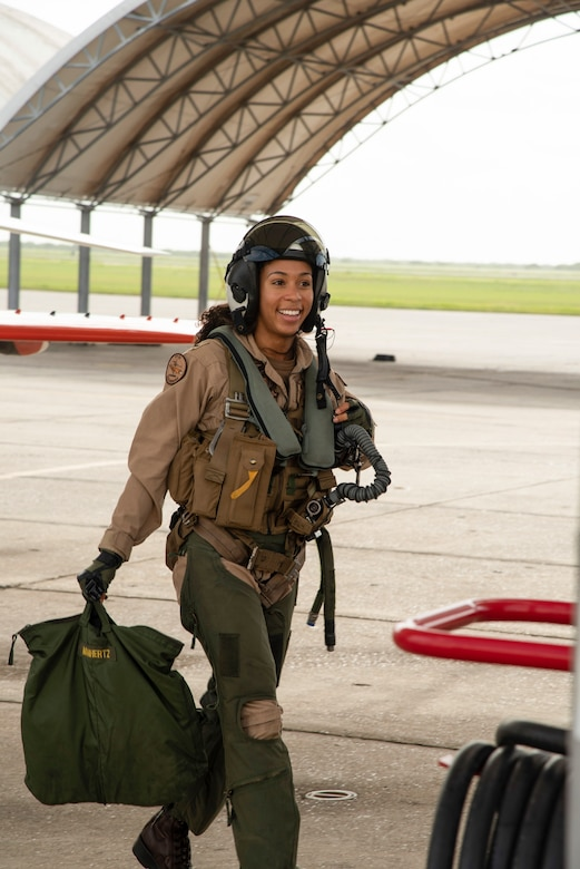 A woman in pilot's gear walks in a hangar.