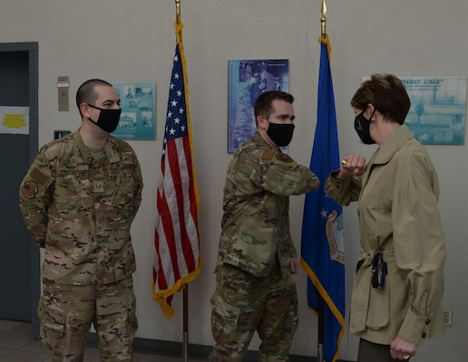 Two Airmen with one bumping elbows with the Secretary of the Air Force.