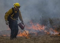 A firefighter with Camp Pendleton Fire Department feeds a prescribed burn in the Juliet Training Area on Marine Corps Base Camp Pendleton, California, May 23, 2020. Firefighters with CPFD are using a series of prescribed burns to clear approximately 50 acres of dense vegetation over the Memorial Day weekend. The fires will improve the habitat for the kangaroo rat, one of 18 endangered species that lives on Camp Pendleton, and prevent wildfires during the summer fire season. (U.S. Marine Corps photo by Lance Cpl. Andrew Cortez)
