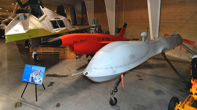 An MQ-1B Predator remotely piloted aircraft on display next to other aircraft in the Hill Aerospace Museum gallery.