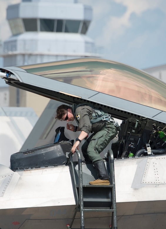 An Air Force F-22 Raptor pilot climbs out of his plane's cockpit Aug. 23, 2020, shortly after his arrival at Wright-Patterson Air Force Base, Ohio. Eight aircraft of the 325th Fighter Wing, out of Eglin Air Force Base, Fla., flew to Wright-Patterson AFB to evade Hurricane Marco and Tropical Storm Laura which are approaching the U.S. Gulf Coast. (U.S. Air Force photo by R.J. Oriez)