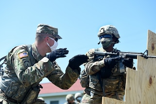 U.S. Army Reserve Sgt. 1st Class Eric Monson, left, observer coach/trainer assigned to the 1st Battalion, 383rd Regiment in Des Moines, Iowa, instructs a Soldier assigned to the 849th Quartermaster Company, Rocky Mount, North Carolina, during Table 3 of the new Army Individual Weapons Qualification standards that will take effect on October 1, 2020.