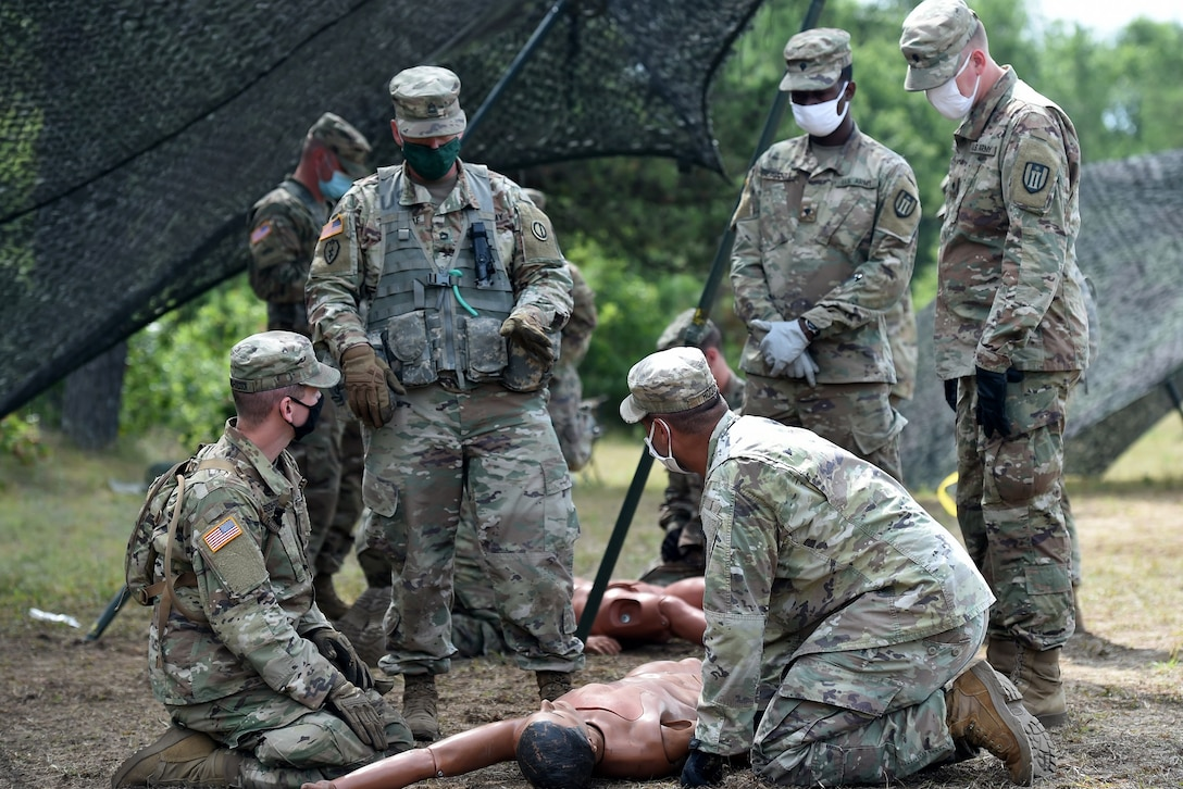 An Army Reserve observer coach/trainer assigned to the 85th U.S. Army Reserve Support Command, observes training on Performing First Aid to Open the Airway for Soldiers from the 623rd Inland Cargo Transfer Company, during Operation Ready Warrior exercise, at Fort McCoy, Wisconsin, August 22, 2020.
