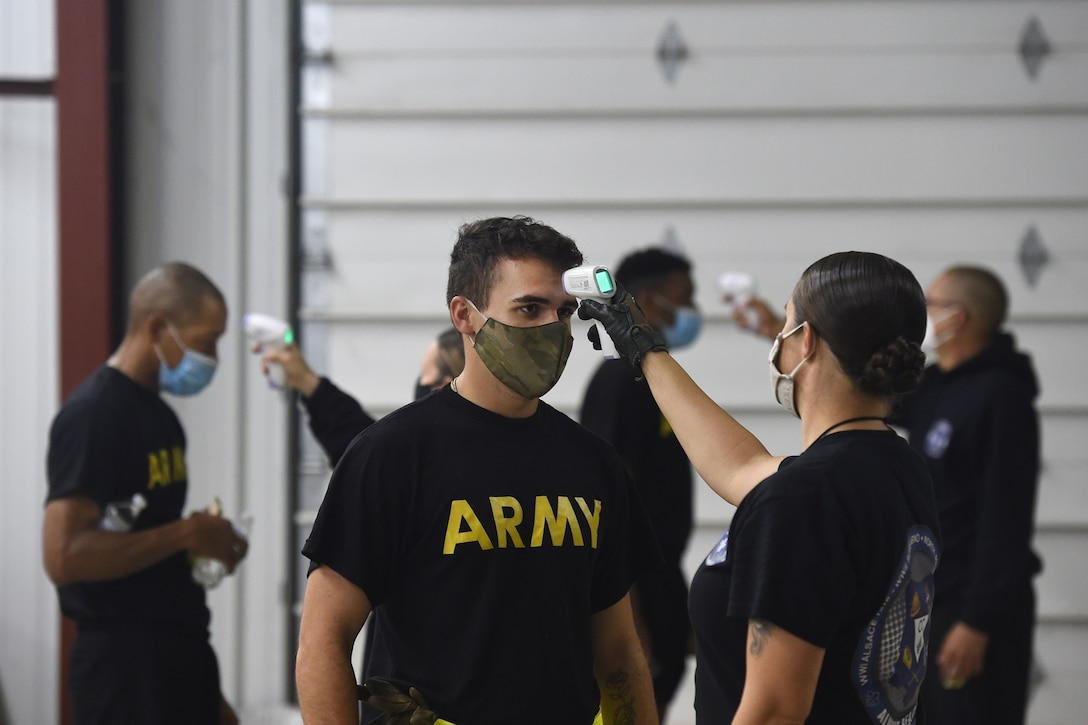 Observer coach/trainers, under First Army's 181st Multi-functional Training Brigade, conduct temperature checks on arriving Soldiers before an Army Combat Fitness Test familiarization at Operation Ready Warrior exercise, at Fort McCoy, Wisconsin, August 23, 2020.