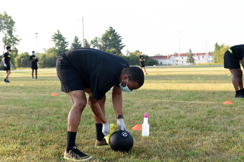 An Army Reserve Soldier sanitizes a 10-pound medicine ball after he uses it for the Standing Power Throw, one of six test events for the Army Combat Fitness Test, during Operation Ready Warrior exercise, at Fort McCoy, Wisconsin, August 23, 2020.