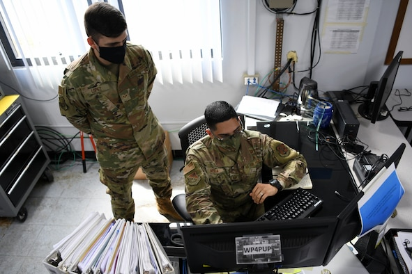 U.S. Air Force Tech. Sgt. Luis Vega and Senior Airman Carlos Lopez, cybersecurity managers with the 156th Communications Flight, Puerto Rico Air National Guard, run software programs from a workstation at Muñiz Air National Guard Base, July 7, 2020.